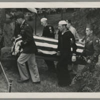 Military pallbearers bearing flag-draped casket