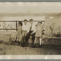 Children sitting on a bridge